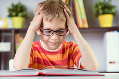 Basisschooljongen bij bureaulezing boock stock fotografie