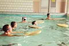 Basisschoolkinderen binnen het zwemmen vaardighedenles stock afbeeldingen