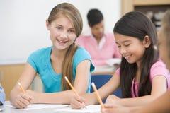 Basisschoolleerlingen in klaslokaal stock foto