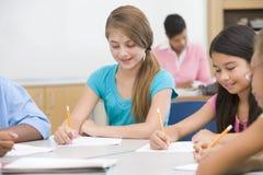 Basisschoolleerlingen in klaslokaal stock afbeeldingen