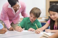 Basisschoolleraar die leerling helpt Stock Fotografie