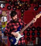 basisty pojęcie Mężczyzna s trzyma basową gitarę, sztuki muzyka w świetlicowym atmosfery tle Muzyk, artysta sztuka elektryczna Zdjęcie Stock