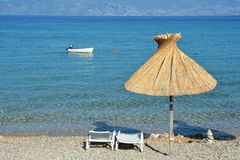 Baska beach. Detail of beach in Baska on island Krk, Croatia - two deck chairs and a parasol stock image