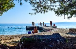 Baska Pole beach, Croatia. Baska Pole, Croatia - July 12, 2018: Vacationers on the public beach and pier of the town of Baska Pole stock image