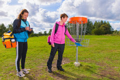 Beside basket. Women beside the basket during the disc golf game Stock Images