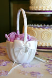 Basket. Flower girl's basket sitting on cake table with purple petals inside Royalty Free Stock Photo