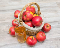 Basket of apples and a glass of juice on a wooden table Stock Image