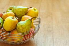 Basket with apples and pears. Metal basket with apples and pears on wooden table royalty free stock photo
