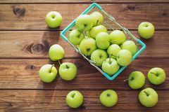 Basket of apples on a wooden table. Basket of apples scattered on a wooden table royalty free stock photo