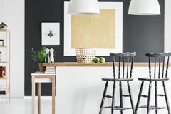 Contrast color kitchen interior. Basket and apples on wooden countertop and black bar stools in contrast color kitchen interior Royalty Free Stock Images