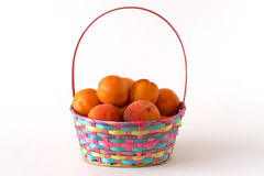 Basket with apricots and peaches. Over white background Royalty Free Stock Photography