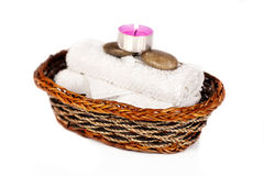 Basket  arrangement. An arrangement of a creel basket with towels, pebbles and a lit candle Royalty Free Stock Images