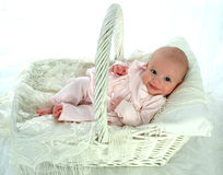 Basket Baby. Baby girl dressed in pink, reclining on pillows in a basket Stock Images