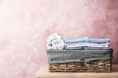 Basket with baby clothes on table near color wall. Space for text stock photo