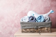 Basket with baby clothes on table. Near color wall. Space for text stock images