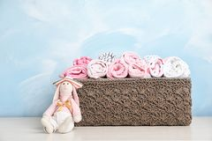 Basket with baby clothes and toy on table. Near color wall stock photo