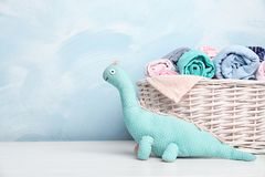 Basket with baby clothes and toy on table. Near color wall. Space for text stock photos