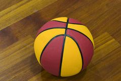 Basket ball. A red and yellow basketball ball on a court Stock Photo