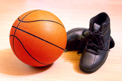Basket Ball. Photo of one basket ball and sneakers in a wooden floor Royalty Free Stock Images