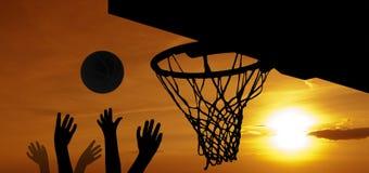 Basket-ball au coucher du soleil Image stock
