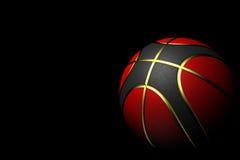Basket-ball d'isolement sur le fond noir avec des couleurs rouges, noires et d'or photographie stock