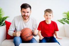 Basket-ball de observation de père et de fils Image stock