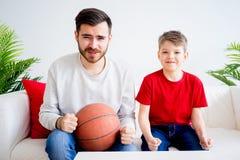 Basket-ball de observation de père et de fils Photographie stock