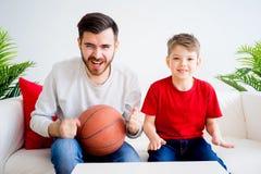 Basket-ball de observation de père et de fils Photos stock
