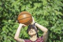 Basket-ball en cuir à disposition d'une femme portant un arbre de tache floue de fond de montre en parc de Yai de coup, Nonthabur photos stock