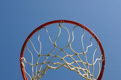 Basket ball hoop from below. Looking up at a basketball hoop against a blue sky Royalty Free Stock Photo