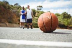 Basket-ball orange sur la terre avec le joueur se tenant à l'arrière-plan Photo libre de droits
