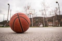 Basket-ball orange utilisé avec le panier à l'arrière-plan Cour de rue de basket-ball Photos stock