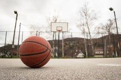 Basket-ball orange utilisé avec le panier à l'arrière-plan Cour de rue de basket-ball Images stock