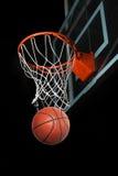 Basket-ball passant par le cercle photographie stock