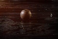 Basket-ball sur la fin humide de plancher de cour avec le fond brouillé Sous la pluie Image stock