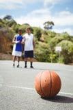 Basket-ball sur la terre avec le joueur se tenant à l'arrière-plan Photographie stock