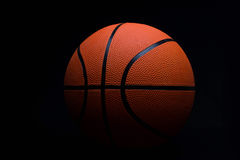Basket-ball sur un fond noir Photo stock