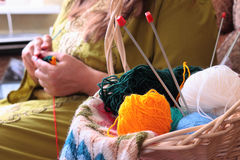 Basket with balls of yarn  and woman knitting Stock Photography