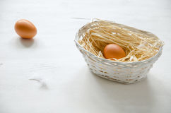 Basket with beige egg. On the white wooden table. Copy-space composition royalty free stock images