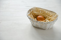 Basket with beige egg. On the white wooden table. Copy-space composition. Focus is on the egg royalty free stock photography