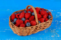 Basket with berries on old boards Stock Photos