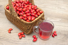 Basket with berries of wild rose and a drink in a glass cup Stock Images