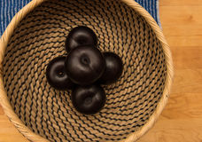 A basket of black plums. On a wood background Stock Image