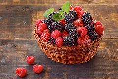 Basket with blackberries, strawberries and raspberries on wooden table. Decorated with mint branch Stock Images