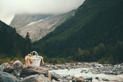 Basket and blanket in mountains. Closeup photo of wicker basket with blanket over mountains view, picnic in cold season Stock Photos