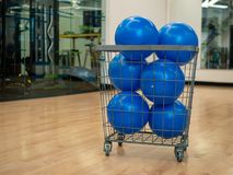 Basket with blue core exercise balls in an exercise studio. Basket filled with blue core exercise balls in an exercise studio royalty free stock images