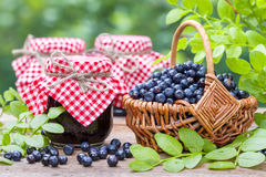 Basket with blueberries and  jars of jam. Stock Photo