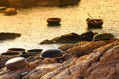 Basket boat of fishermen on rocky coast Royalty Free Stock Images