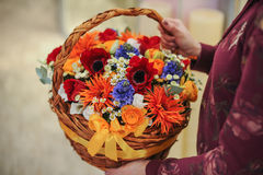 Basket with a bouquet of colorful flowers. In hands Stock Photos