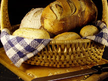 Basket of bread. Some exotic breads and rolls in a wicker basket on a cutting board on a black backround stock photo